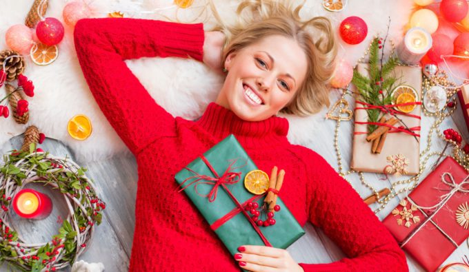 48971442 - happy woman lying on the floor with gift box in hand