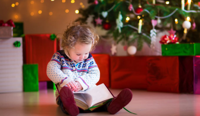 31615573 - cute curly little toddler girl in a warm knitted sweater sitting on a floor next to a christmas tree reading a book enjoying cozy winter day at home