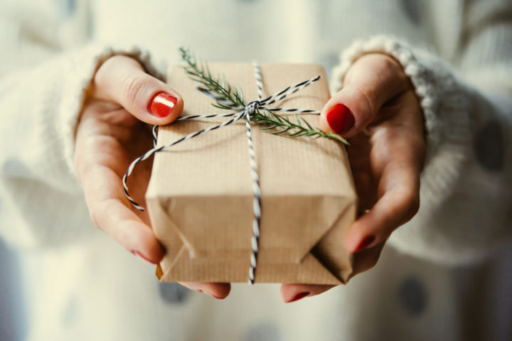 50646104 - woman's hands hold christmas or new year decorated gift box. toned picture